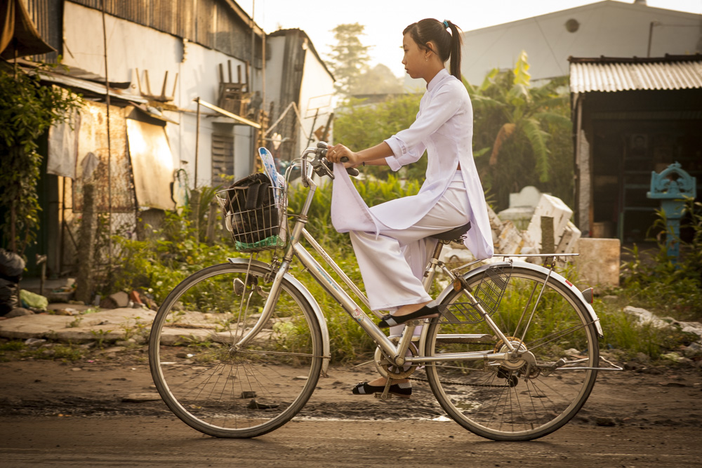 Young student wearing ao dai on bicycle. An Giang, Vietnam