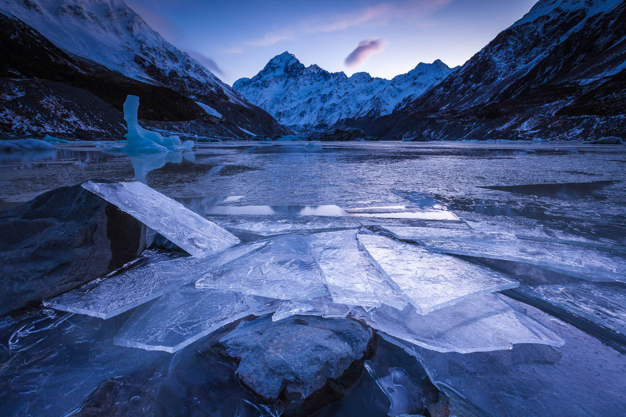 Broken ice, piled by the wind and waves. I spent the evening camped on the edge of this lake in sub zero conditions with the lake calm and frozen, The wind turned NW (warm & gusty) during the night and  broke the ice, throwing great sheets onto the shore. Hooker Glacier terminal lake and Aoraki Mount Cook. Hooker Valley, Aoraki Mount Cook National Park.